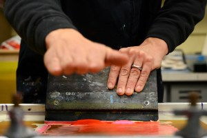 Jordan explained how a print needs a consistent pressure and angle for the ink to be applied properly. Here he motions how he pushes the ink rather than pulling it, leaving less strain on his wrists over time. Photo by Annie Lomshek