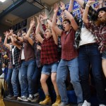 """Students in the stands raise their arms and cheer during the """"Hit the Court Like"""" chant before the game. Photo by Diana Percy"""