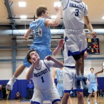 A Rockhurst player grabs the ball out of the air while senior Stanley Morantz falls onto the back of a Rockhurst player after taking a shot. Photo by Diana Percy