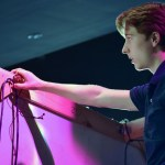 Freshman Nick Edge adjusts wires on a set piece during a light test. Photo by Audrey Kesler