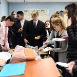 The third hour European History class gathers around the front table to makes plates of French food. Photo by Haley Bell