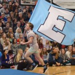 "Senior Jake Randa sprints across the junior section, holding up the giant ""E"" flag. Photo by Grace Goldman"