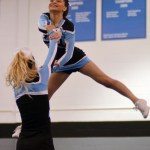 Junior Astrid Cifuentes performs a toe touch twist in the varsity cheerleading performance. Photo by Izzy Zanone