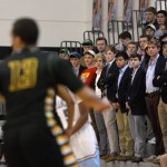The East student section looks on as a West player advances towards the basket. About thirty to forty students showed up to watch the game. Photo by Celia Hack