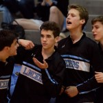 Juniors Jack Workman, Will Curran, Ben Dollar and Seamus Caroll cheer on the varsity basketball team as they head into overtime against Lawrence. Photo by Katherine Odell