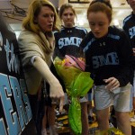 Junior Libby Frye grabs flowers and is directed on how to present them before the girls' basketball senior night. The seniors this year are Quincy Bair, Kyle Haverty, Tyler Keys and Josie Clough. Photo by Diana Percy