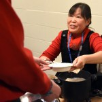 Ms. Lau smiles as she dishes up her freshly made dumplings. Photo by Ellie Thoma