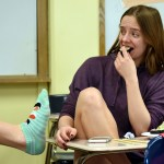 Junior Grace Apodaca makes a face of disgust and junior Anna Kanaley shows her the sushi socks she is wearing. Photo by Ellie Thoma