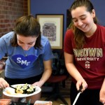 Juniors Anna Kanaley and Ellie Van Gorden laugh as they put together plates of sushi to deliver to some of their teachers. Photo by Ellie Thoma