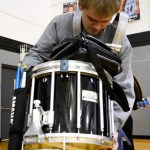 Senior Xan Denniston packs up his drums at the end of the game.  Photo by Annie Lomshek