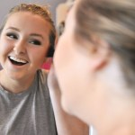 Finishing her makeup, sophomore Holly Frigon laughs in the mirror after her friend made a funny comment. Photo by Grace Goldman