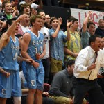 After senior Jack Schoemann makes a three-pointer in the third quarter to tie up the game, juniors Jack Workman and Seamus Carroll, seniors Connor Rieg and Stanley Morantz, and coach Shawn Hair celebrate on the sideline. Photo by Lucy Morantz