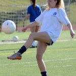 Junior Jade Daly-Roentved kicks the ball to her teammate in a warm up drill. photo by Ellen Swanson