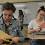 Concentrating hard, freshmen Emma Wiltfong and Mary McConville work on cutting out their masks. Photo by Grace Goldman