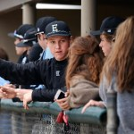 In the dugout, junior Christian Flathman explains the rules of baseball to the team managers. Photo by Kaitlyn Stratman