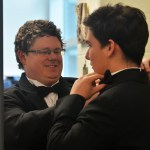 Band director Alex Toepfer helps a student adjust their bow tie. Photo by Libby Wilson