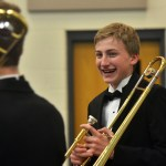 Freshman Palmer Bowles and fellow band members tune their trombones in the time leading up to the concert. Photo by Libby Wilson