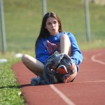 Sophomore, Emily Giron, takes off sweatpants before warming up for track practice. Photo by Ava Simonsen