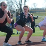 Sophomore Peyton Lindsey, junior Brittany Bahr, and senior Hope Dunn do squats wile warming up for track. Photo by Ava Simonsen