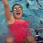 Sophomore Riley Kimmel laughs as she pushes off of the wall into her backstroke streamline. Photo by Reilly Moreland