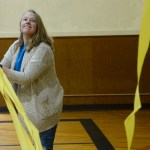 Sophomore Sadie Osborn helps take down the decorative streamers after the fundraiser is over. Photo by Luke Hoffman