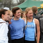 Senior Devon Dietrich, sophomore Kara Mccaskey and juniors Madeline Hlobik and Ingrid Worth get their picture taken by their coach after they finished running and winning the relay race. Photo by Katherine Odell