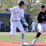 Senior Henry Sullivan runs to beat Olathe's first base-man to the base. Photo by Diana Percy