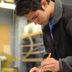 Drawing marks with a pencil, senior Tony Salinas measures out where he needs to cut the wood. Photo by Grace Goldman