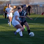 After running to get the ball, sophomore Izzy Rapp makes it to the ball first and gets possession of the ball over her opponent. Photo by Katherine Odell