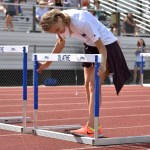 Sophomore Dasha Hamilton helps set up the hurdles in preparation for the 100 meter girls hurdles race. Photo by Laini Reynolds