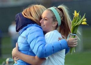 Senior Libby Legard hugs her mom after handing her flowers for senior night. Photo by Katherine Odell