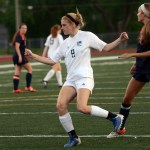 Senior Lily Flint runs to kick the ball in hopes of scoring a goal against Olathe East. Photo by Katherine Odell
