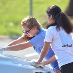 Juniors Emma Broaddus and Lia Miller wash the hood of a car. Photo by Ally Griffith