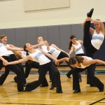 Sophomore Ellie Brown does a leg hold while the JV dance team poses around her. Photo by Ellen Swanson