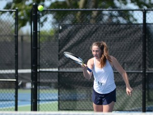 Freshman Abby Carter does an underhand swing to hit the ball. Photo by Reilly Moreland
