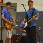 Seniors Cal Knabe and Sam Fay play their guitars while smiling at the crowd. Photo by Katherine Odell