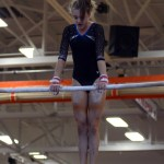 During her bar routine, junior Emily Eadens jumps to the high bar and does a cast into a push away kip. Photo by Aislinn Menke
