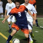 Senior Ian Schutt pressure the Olathe East forward opponent. Photo by Audrey Kesler