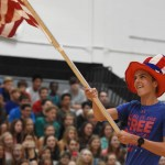 Junior Tom Joyce runs out wearing an American themed outfit waving an American flag. Photo by Ellen Swanson