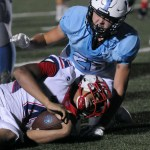 Junior Garrett Boschen tackles an Olathe North Eagle to keep them from advancing towards the end zone. Photo by Izzy Zanone