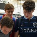 Juniors Will Tulp, Tom Joyce, and Culley Woods and sign up for a share project at the care fair during seminar. Photo by Katherine Odell