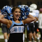 Sophomore Gabby Mack puts her cheer poms on her head during a cheer. Photo by Reilly Moreland