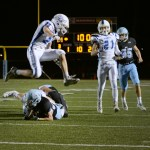 A Gardener player jumps over junior Ryan Hess after he is tackled carrying the ball. Photo by Diana Percy