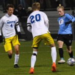 Senior Bennett Meeds kicks the ball away from the Olathe South players. Photo by Carson Holtgraves