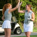 Junior Kailey Rawson high-fives senior Allison Benson after a good swing. Photo by Izzy Zanone