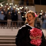 Sophomore Ellie Phillips looks around as the everyone in the student section hold up their phone flashlights. Photo by Ellie Thoma