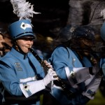 Junior Trinity Legill laughs while playing her clarinet as the tarp begins to cover the band. Photo by Ellie Thoma