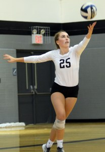 Focused on the ball, senior Ally Huffman serves the ball over the net. Photo by Kate Nixon