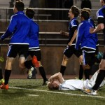After the Ravens score in the first half of golden goal stoppage time, senior Bennett Meeds lays on the field while Northwest players run over to the stands to celebrate their win. Photo by Lucy Morantz