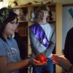Junior Jia Self holds the sacrificial pomegranate before they cut it open. Once it was cut open, each inductee ate one of the seeds. Photo by Ally Griffith
